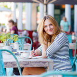 Woman drinking coffee and writing notes in cafe Stock Image