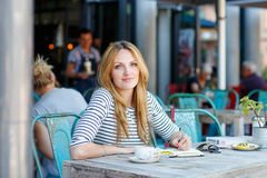 Woman drinking coffee and writing notes in cafe Stock Photos