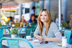 Woman drinking coffee and writing notes in cafe Royalty Free Stock Images
