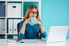 Woman drinking coffee. Young woman drinking coffee in the office Royalty Free Stock Photography