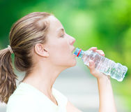 Woman drinking cold mineral water from a bottle after fitness ex Stock Images