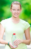 Woman drinking cold mineral water from a bottle after fitness ex Royalty Free Stock Photo