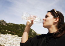 Woman drinking crystal clear water from bottle Royalty Free Stock Image