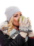 Woman drinking from cup. A attractive blond woman dressed for winter is drinking from a coffee cup stock photo