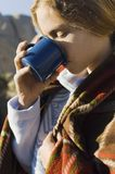 Woman Drinking from Cup Clutching Blanket Royalty Free Stock Photography