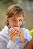 Woman drinking a cup of coffee. Young caucasian woman with a cup of coffee, outdoors Royalty Free Stock Image