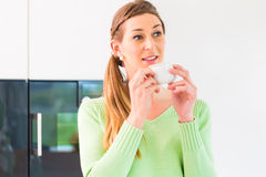 Woman drinking cup of coffee in kitchen Stock Photography