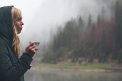 Woman drinking a cup of coffee in outdoor setting. Horizontal side view portrait of Caucasian young blonde woman wearing a hooded dark blue jacket and drinking a Stock Image
