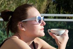 Woman Drinking A Cup Of Coffee Outdoors In The Sun Royalty Free Stock Images