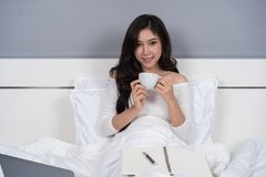 Woman drinking a cup of coffee and using laptop computer on bed stock photography