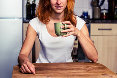 Woman drinking from cup in her kitchen Royalty Free Stock Image