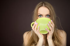 Woman drinking from a cup Royalty Free Stock Images