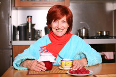 Woman drinking a cup of tea with raspberry jam Stock Photography