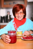 Woman drinking a cup of tea with raspberry jam Royalty Free Stock Photos