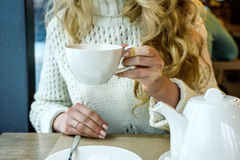 Woman drinking a Cup of tea in the restaurant. Winter leisure, cold weather, hot drink. Woman drinking a Cup of hot tea in the restaurant. Winter leisure, cold Royalty Free Stock Photos