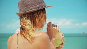 Woman drinking fresh coconut water with straw on beach fun vacation. Closeup of woman holding young green tropical fruit sipping for healthy snack during stock video