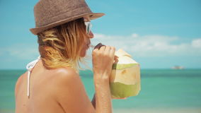 Woman drinking fresh coconut water with straw on beach fun vacation. Closeup of woman holding young green tropical fruit sipping for healthy snack during stock footage