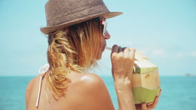 Woman drinking fresh coconut water with straw on beach fun vacation. Closeup of woman holding young green tropical fruit sipping f stock footage
