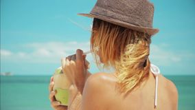 Woman drinking fresh coconut water with straw on beach fun vacation 3 shots. Woman drinking fresh coconut water with straw on beach fun vacation. Closeup of stock footage