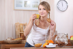 Woman drinking fruit juice. Blond woman drinking fruit juice and eating a biscuit Stock Images