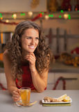 Woman drinking ginger tea in christmas decorated kitchen Royalty Free Stock Photos