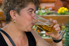 Woman drinking a glass of beer. Outdoors stock photo