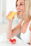 Woman drinking glass of orange juice Stock Photos