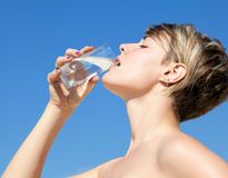 Woman drinking a glass of water Royalty Free Stock Photos