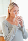 Woman drinking a glass of water in the kitchen Stock Images