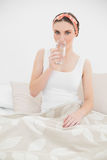Woman drinking a glass of water looking into the camera Royalty Free Stock Image
