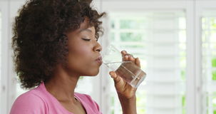 Woman drinking glass of water and smiling