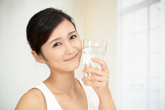 Woman drinking a glass of water. The young woman drinking a glass of water stock images