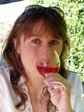 Woman drinking glass of wine. A woman drinking a large glass of rose wine outside on a sunny summers day, bright blue eyes looking at the camera, displaying a Royalty Free Stock Images