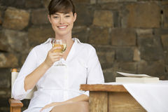 A woman drinking a glass of wine sitting at a table Royalty Free Stock Image