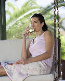 A woman drinking a glass of wine on a swing Royalty Free Stock Images