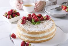 Woman drinking green tea and eating tasty sponge cake with strawberries.Tea party. Waiter pourig hot water onto the tea bag. Tea time, delicious sponge cake with royalty free stock images