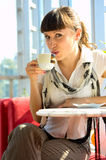 Woman drinking hot coffee. Beautiful woman drinking hot coffee in sunny cafe Stock Photos