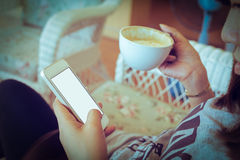 Woman drinking hot coffee in cafe and use a mobile phone stock photography