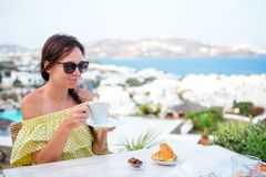 Woman drinking hot coffee on luxury hotel terrace with sea view at resort restaurant. Stock Images