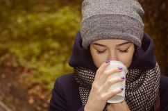 Woman drinking hot coffee in the park. Young woman drinking hot coffee in the dark autumn park Royalty Free Stock Photo