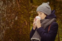 Woman drinking hot coffee in the park. Young woman drinking hot coffee in the dark autumn park Stock Photos
