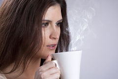 Woman drinking a hot drink Stock Photography