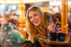 Woman drinking hot punch on German Christmas market. Royalty Free Stock Image