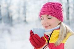 Woman drinking hot tea. Beautiful blond woman drinking hot tea outdoors Stock Photography