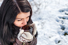 Woman drinking hot tea. Attractive young female dressed up warm wearing mitten and drinking hot tea Stock Image