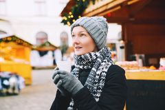 Woman drinking hot tea or mulled wine at Christmas in Europe. Beautiful young woman drinking hot ginger tea or mulled wine from cup at Christmas market in old Stock Image