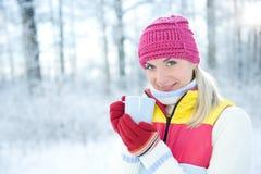 Woman drinking hot tea outdoors. Beautiful blond woman drinking hot tea outdoors Stock Images