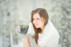 Woman drinking hot tea in winter forest Stock Photo