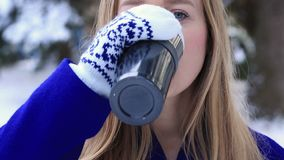 Woman drinking hot wine from thermocup in winter stock footage