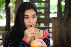 Woman drinking ice tea from plastic cup with straw at cafe. Close up of asian woman in blue dress drinking ice tea from plastic cup with straw at cafe royalty free stock photo